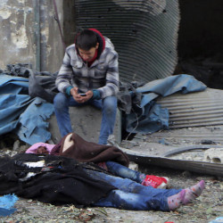 A Syrian boy sits beside bodies after artillery fire struck eastern Aleppo, Syria, on Wednesday. Fighters on both sides will do anything to gain military advantage, a U.N. chief says.