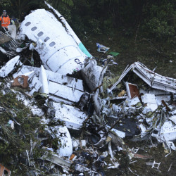 Rescue workers stand at the wreckage site of the chartered airplane that crashed in a mountainous area outside Medellin, Colombia, Tuesday, killing 71 of the 77 people on board.