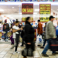 Shoppers stream past advertisements for Black Friday sales at the Maine Mall Friday afternoon.
