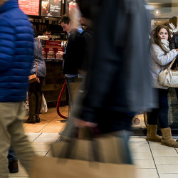 Lily Rubin, 11, of Gorham, clings to her mother Karen, at right, as they shoppers stream past and they wait to meet friends from New York City at the Maine Mall on Black Friday.