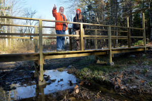 Dennis Hawkes, founding member of the Windham Land Trust, and Rachelle Curran Apse, executive director of the Presumpscot Regional Land Trust, look out over a new 100-acre preserve in Windham from a bridge over Black Brook.