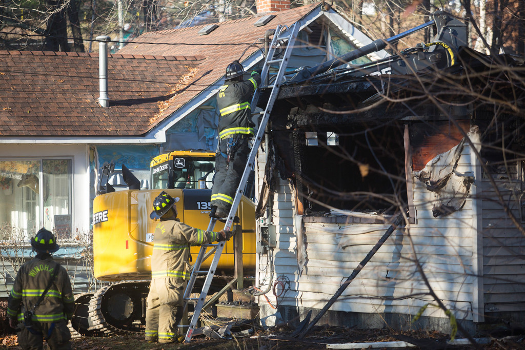 Firefighters conduct cleanup operations at 10 Pettingill Road while investigators examine the structure to try to find out what started the blaze that killed Marie McAllister Friday morning.