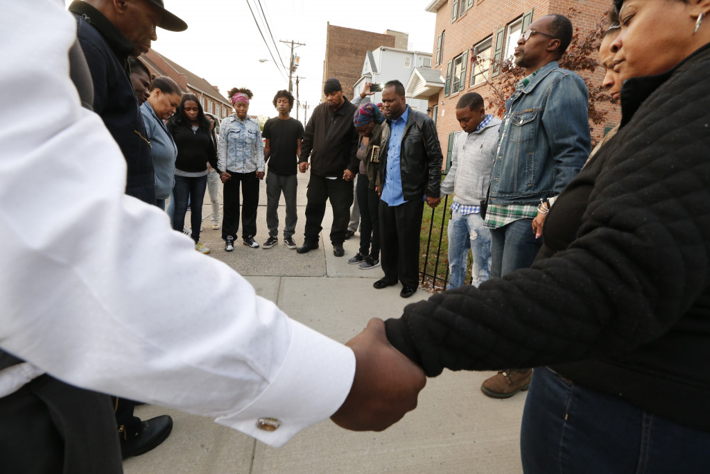 Neighbors hold hands in prayer after three people were killed and several others injured in a stabbing at a house in Newark, N.J., on Saturday.  Robert Sciarrino/NJ Advance Media for NJ.com via AP