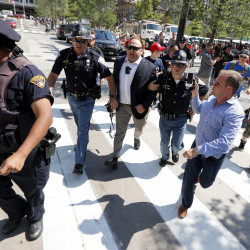 Alex Jones, center, a conspiracy theorist and radio show host, is escorted out of a crowd of protesters after he said he was attacked in Public Square on July 19, 2016, in Cleveland, during the Republican National Convention.