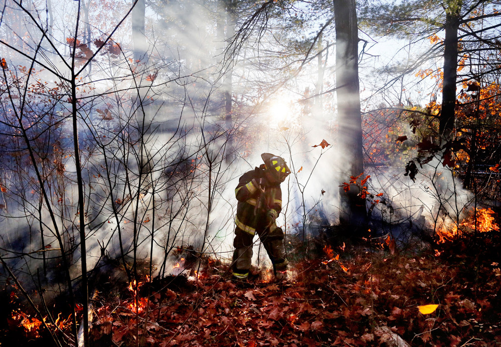 Jeremy Dowd, an intern at the Scarborough Fire Department, battles a brush fire along the railroad tracks near Highland Avenue and Black Point Road on Friday afternoon.