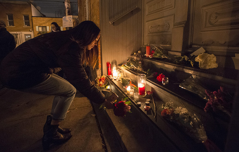 A woman places a candle in front of the home of singer and poet Leonard Cohen in Montreal Thursday evening.