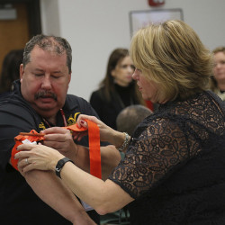 Two staffers at a school in Stony Brook, N.Y., practice applying a tourniquet to one another during a first aid training session at Stony Brook University.