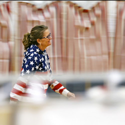 Linda Case, Falmouth's deputy town clerk, strides through the polling location at Falmouth High School to answer a voter's question.