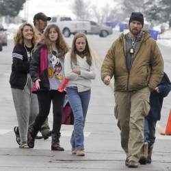 Associated Press/Rick Bowmer A police officer escorts students after a school lockdown at Mueller Park Junior High School on Thursday in Bountiful, Utah.