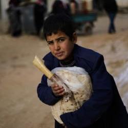 A displaced Syrian boy holds a sandwich and bread bag in the village of Jibreen south of Aleppo, Syria, on Saturday. Aid agencies say that more than 30,000 people have fled rebel-held eastern neighborhoods of Aleppo.