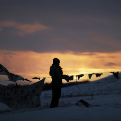 A woman watches the sunset at the Oceti Sakowin camp where people have gathered to protest the Dakota Access oil pipeline in Cannon Ball, N.D., Friday.