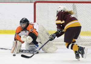 Biddeford/Thornton Academy goalie Bekah Guay dives for the puck as Sophie Miller of Cape Elizabeth/Waynflete/South Portland moves in during a girls' hockey game Saturday afternoon at Biddeford Ice Arena. Cape Elizabeth/Waynflete/South Portland won in overtime, 1-0.