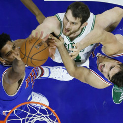 Tyler Zeller, center, of the Celtics battles for a rebound with Philadelphia's Jahlil Okafor, left, and Dario Saric during the first half of Saturday's game in Philadelphia. (Associated Press/Matt Slocum)