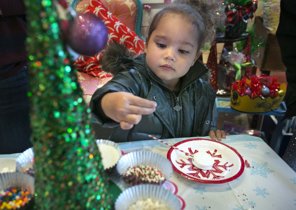 Zola Court-Dickerson, 3, picks out a new topping for an Oreo lollipop dipped in white chocolate that she was decorating during Christmas Prelude in Kennebunk on Saturday. Gregory Rec/Staff Photographer