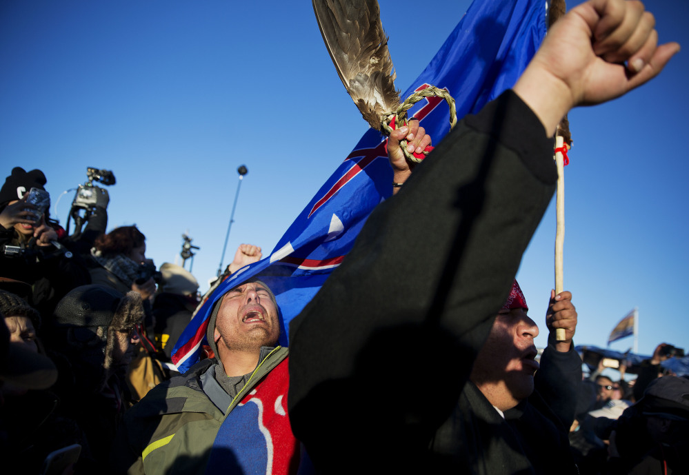 Members of a Native American drum procession celebrate at the Oceti Sakowin camp after it was announced that the U.S. Army Corps of Engineers won't grant easement for the Dakota Access oil pipeline in Cannon Ball, N.D., on Sunday.