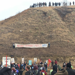 Armed police convene on top of Turtle Island in North Dakota as protesters stand in solidarity with the Standing Rock Sioux, who are fighting to protect their water source by blocking the Dakota Access Pipeline. Among the protesters has been May Aihua Ye, a Waterville native.