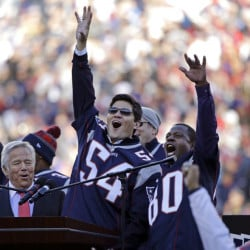 Tedy Bruschi, center, and Troy Brown, right, cheer with the New England Patriots' owner, Robert Kraft, while being honored at halftime Sunday, coming together 15 years after leading the franchise to the first of its four Super Bowl championships.