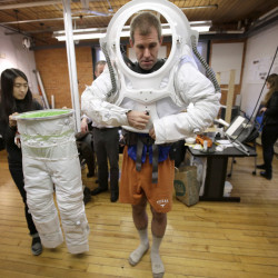 Erica Kim, left, an industrial and apparel design student at the Rhode Island School of Design, helps Andrzej Stewart, the chief engineering officer on a year-long Mars simulation mission that ended in August, put on a new space suit designed by the school.