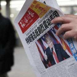 "FILE - In this Nov. 10, 2016 file photo, a man reads a newspaper with the headline that reads ""U.S. President-elect Donald Trump delivers a mighty shock to America"" at a newsstand in Beijing. With Trump's latest tweets touching on sensitive issues, China must decide how to handle an incoming American president who relishes confrontation and whose online statements appear to foreshadow shifts in foreign policy. China awoke Monday, Dec. 5, to criticism from Trump on Twitter, days after it responded to his telephone conversation with Taiwan's president by accusing the Taiwanese of playing a ""little trick"" on Trump. (AP Photo/Andy Wong, File)"