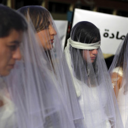 Lebanese women in wedding gowns stained with fake blood, some wearing bandages, stand in front of a government building in Beirut, Lebanon, on Tuesday. They called for repeal of a law allowing a rapist to go free if he marries his victim.
