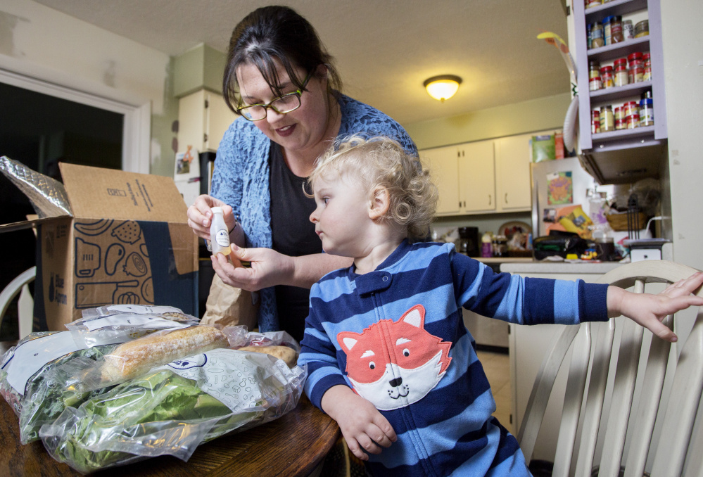 Emily Griffin of Lisbon Falls unpacks a Blue Apron meal kit as her 2-year-old son, Everett, watches. She uses the delivery service for
