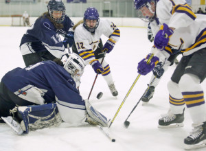 Ruth Lewandowski of Portland/Deering makes a save as Elizabeth Cain, center, and Lilly Wolff of Cheverus/Kennebunk/Old Orchard Beach try to score during Cheverus/Kennebunk/OOB's 12-3 win Wednesday in Portland.