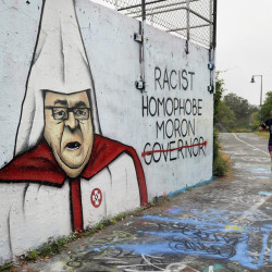 A controversial depiction of Gov. Paul LePage in Ku Klux Klan garb was painted in September on the Portland Water District's wall along the Eastern Promenade Trail in Portland. Now, the district's trustees are considering a ban on graffiti on the wall.