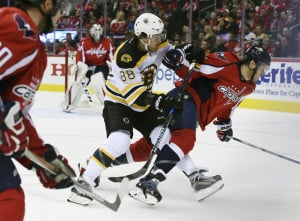 Boston's David Pastrnak trips Capitals defenseman John Carlson in the first period Wednesday night in Washington.