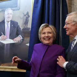 Hillary Clinton smiles as Senate Minority Leader Sen. Harry Reid poses her for a photograph during a farewell ceremony to unveil a portrait of Reid on Capitol Hill on Thursday.
