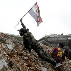 A Syrian soldier places a Syrian flag during a battle with rebel fighters at the front line, east of Aleppo, on Monday. The city appears all but recaptured by President Bashar Assad.