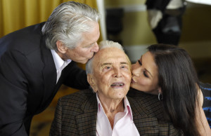 Actor Kirk Douglas, center, gets a kiss from his son Michael Douglas, left, and Michael's wife, Catherine Zeta-Jones, during his 100th birthday party at the Beverly Hills Hotel on Friday in Beverly Hills, Calif.