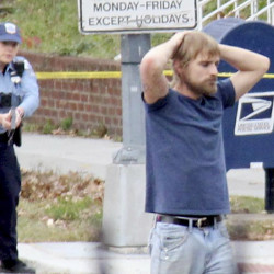 Edgar Maddison Welch, 28, of Salisbury, N.C., surrenders to police Sunday in Washington. Welch allegedly fired an assault rifle inside the restaurant on Sunday, injuring none.