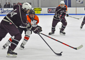 Greely defenseman Ryan Sullivan, left, tries to stop Gardiner forward Matthew Poirier during Saturday's game at Camden National Bank Ice Vault in Hallowell. Joe Phelan/Kennebec Journal