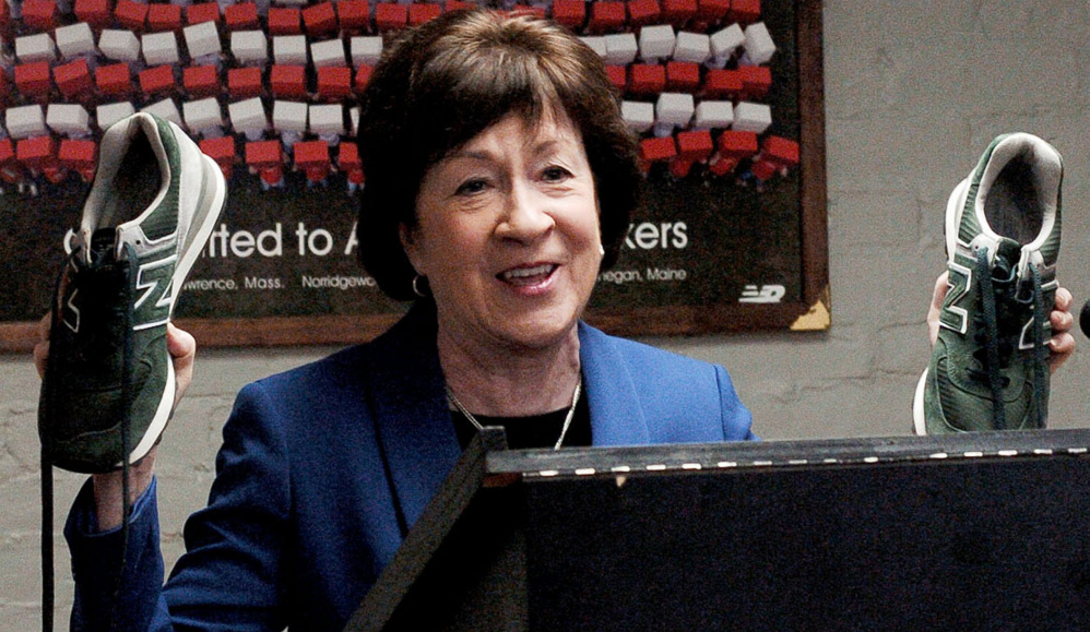 Sen. Susan Collins holds up a pair of New Balance sneakers monogrammed with her husband's initials during.