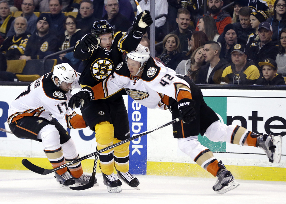 Bruins right wing David Backes gets squeezed between Ducks center Ryan Kesler (17) and defenseman Josh Manson in the second period. Anaheim took the lead in the period and never gave it up.