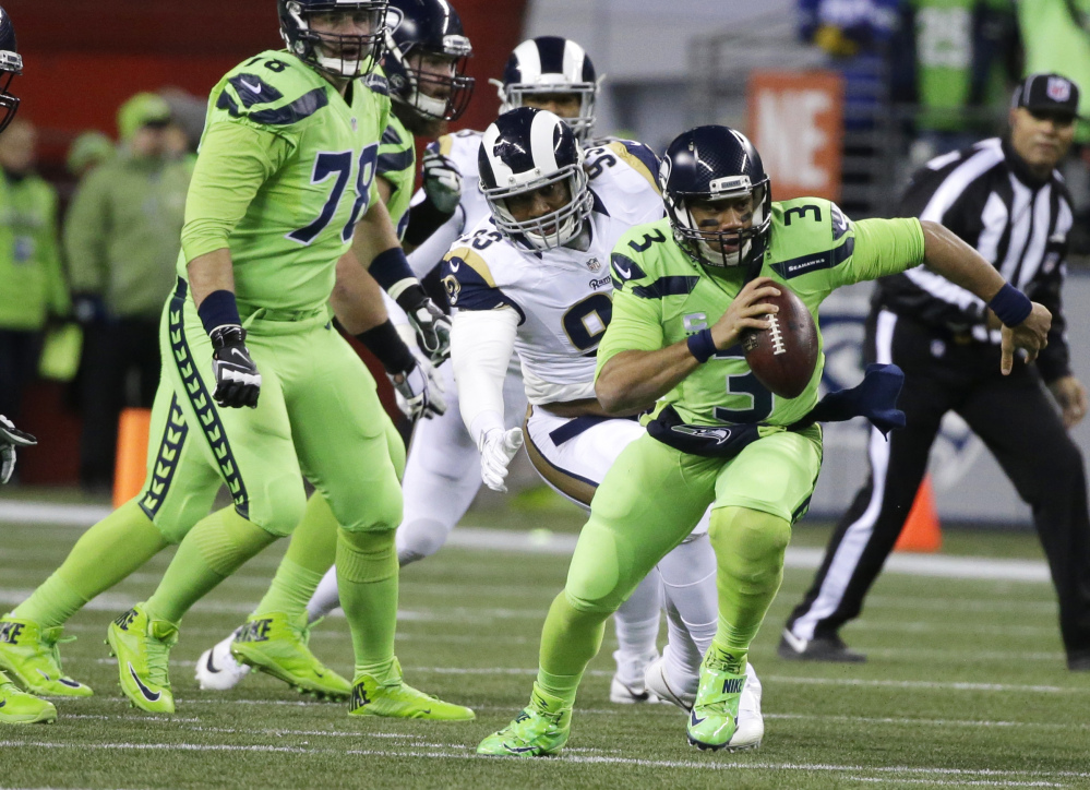 Seattle Seahawks quarterback Russell Wilson threw for three touchdown passes on a 24-3 win over the Los Angeles Rams on Thursday in Seattle. (Associated Press/Elaine Thompson)