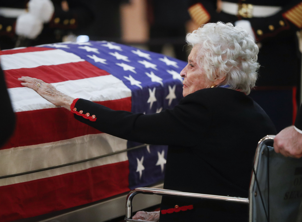 Annie Glenn touches the casket of her late husband John Glenn as he lies in honor Friday in Columbus, Ohio.