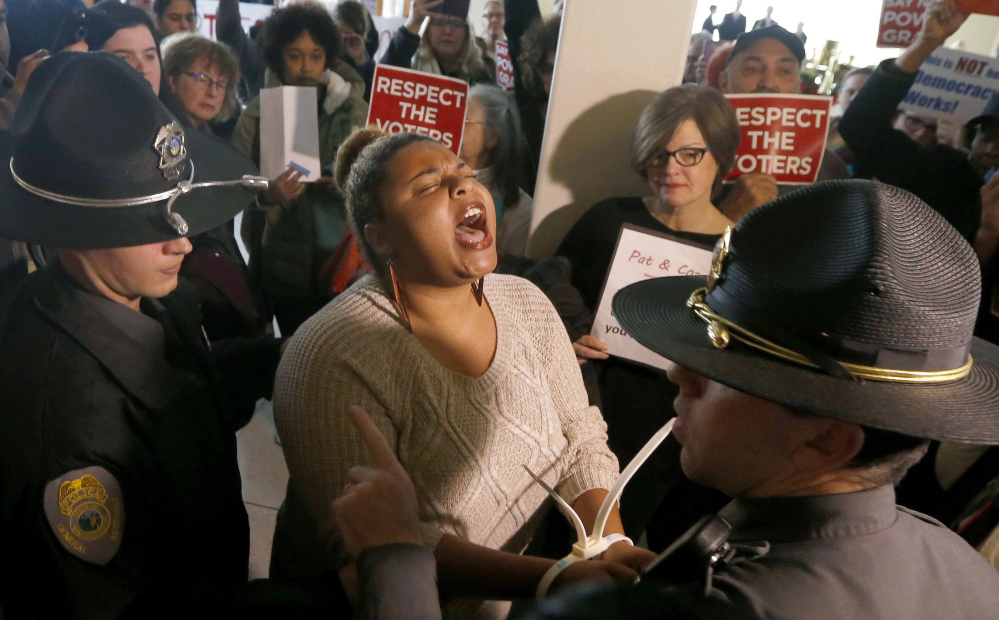 A protester is one of more than 50 arrested outside the House gallery during a special session of the North Carolina General Assembly in Raleigh on Friday.