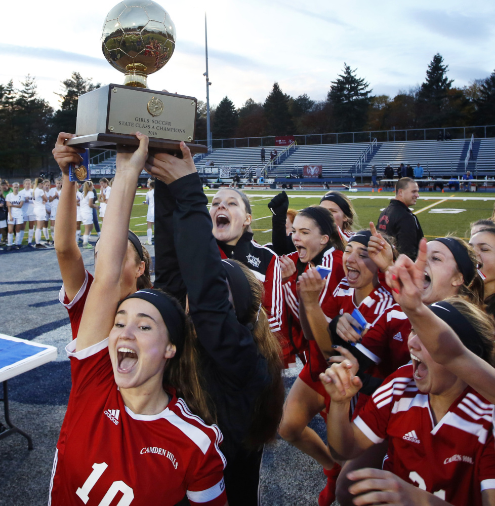 Charlotte Messer, left, and her Camden Hills teammates hoisted the Gold Ball after a 1-0 win over Gorham in the Class A state final, and it was Messer who scored the only goal, in overtime.