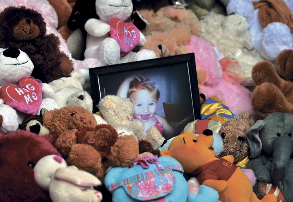 A picture of Ayla Reynolds sits among a shrine of teddy bears in December 2013 on the steps of the Waterville City Hall during a vigil for the missing toddler at Castonguay Square in downtown Waterville.