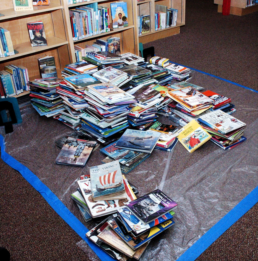 Children's books lay on a tarp at the Waterville Public Library on Monday after a water pipe broke and flooded the library building and damaged books over the weekend.