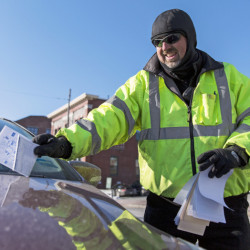 Erik Carlstrom, parking enforcement officer, sticks a ticket under a wiper blade on Commercial Street in Portland. The toughest part of the job, he says, is when conflicts arise between officers and motorists.