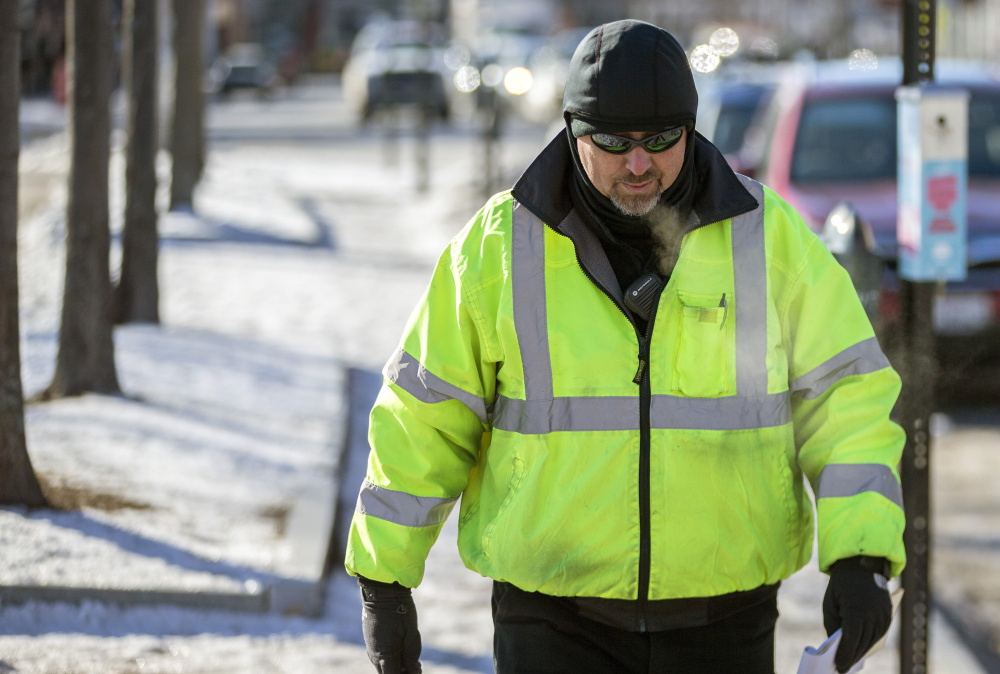 Erik Carlstrom, parking enforcement officer, exhales steamy breath as he walks along Commercial Street in Portland while temperatures were in the single digits.
