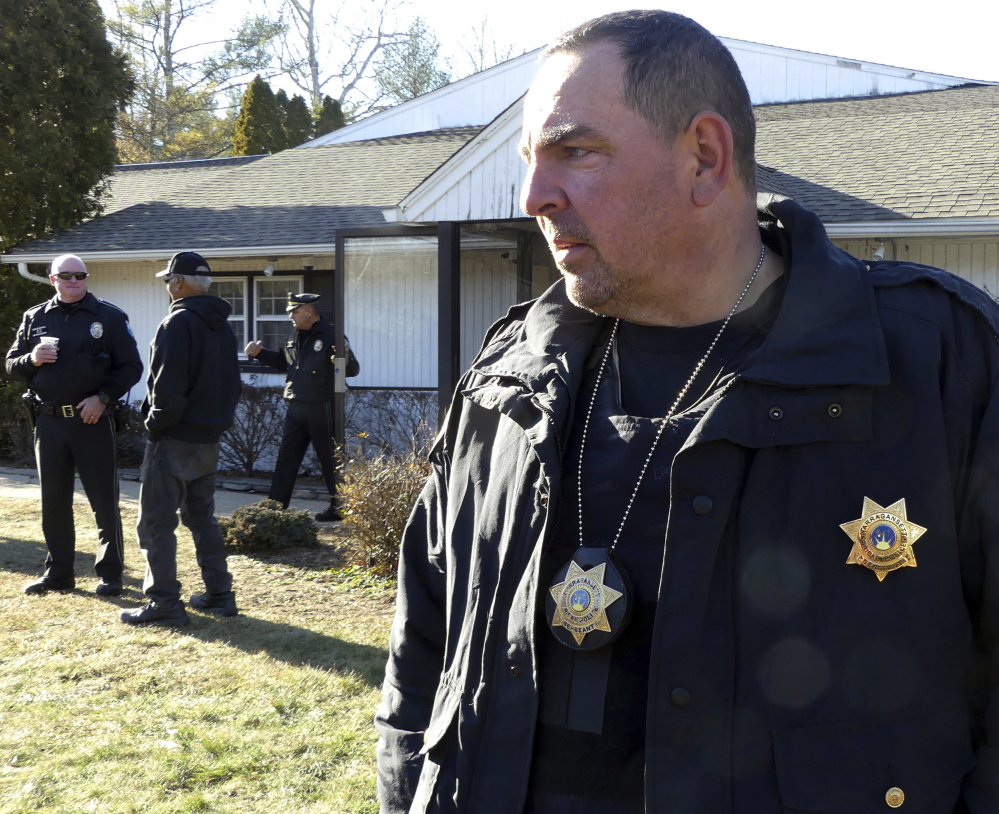 Narragansett Tribal Police Sgt. Ed McQuaide stands outside an entrance to the Narragansett tribe's administration building in Charlestown, which has been occupied.