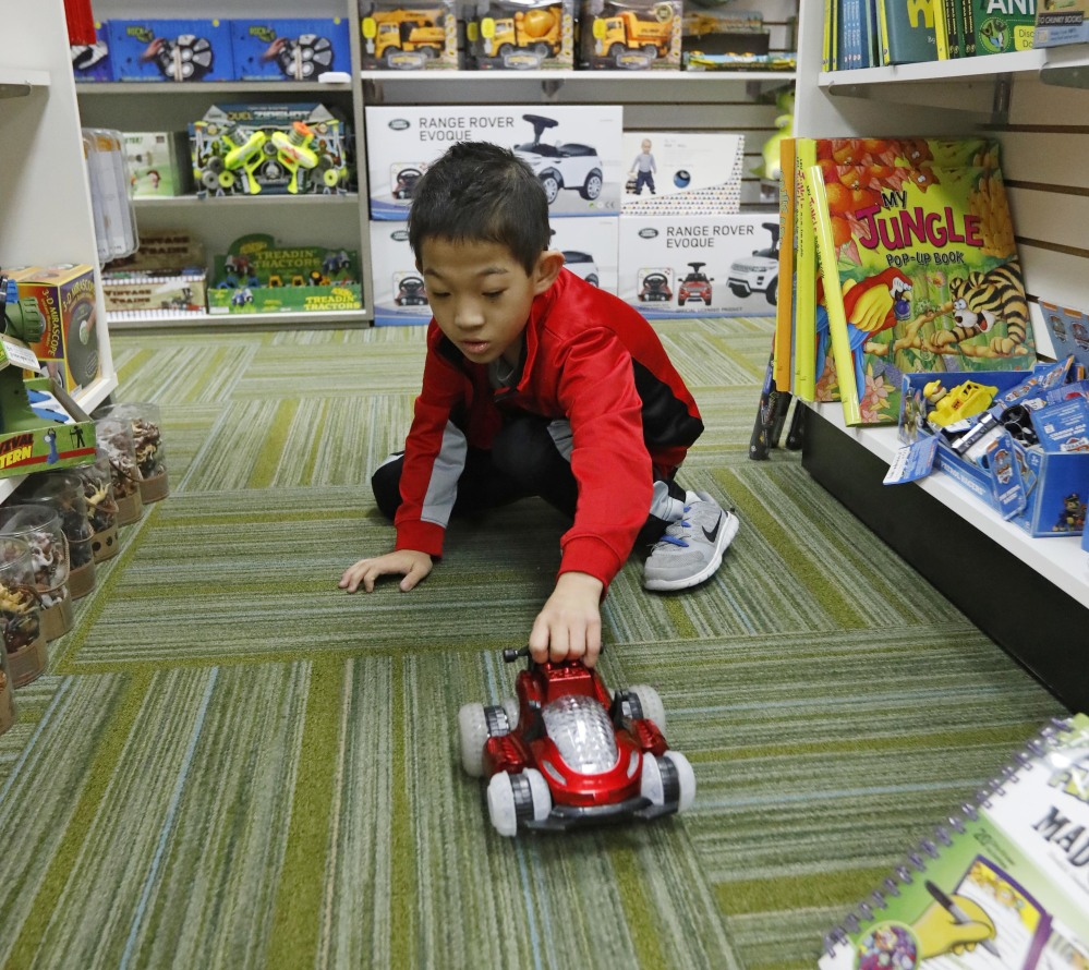 Paxton Mathis, 8, plays with a remote car at Time 4 Toys, in Flowood, Miss. The youngest child of the owner, Paxton, who has sensory processing disorder, often tests out some of the multipurpose toys for sale.