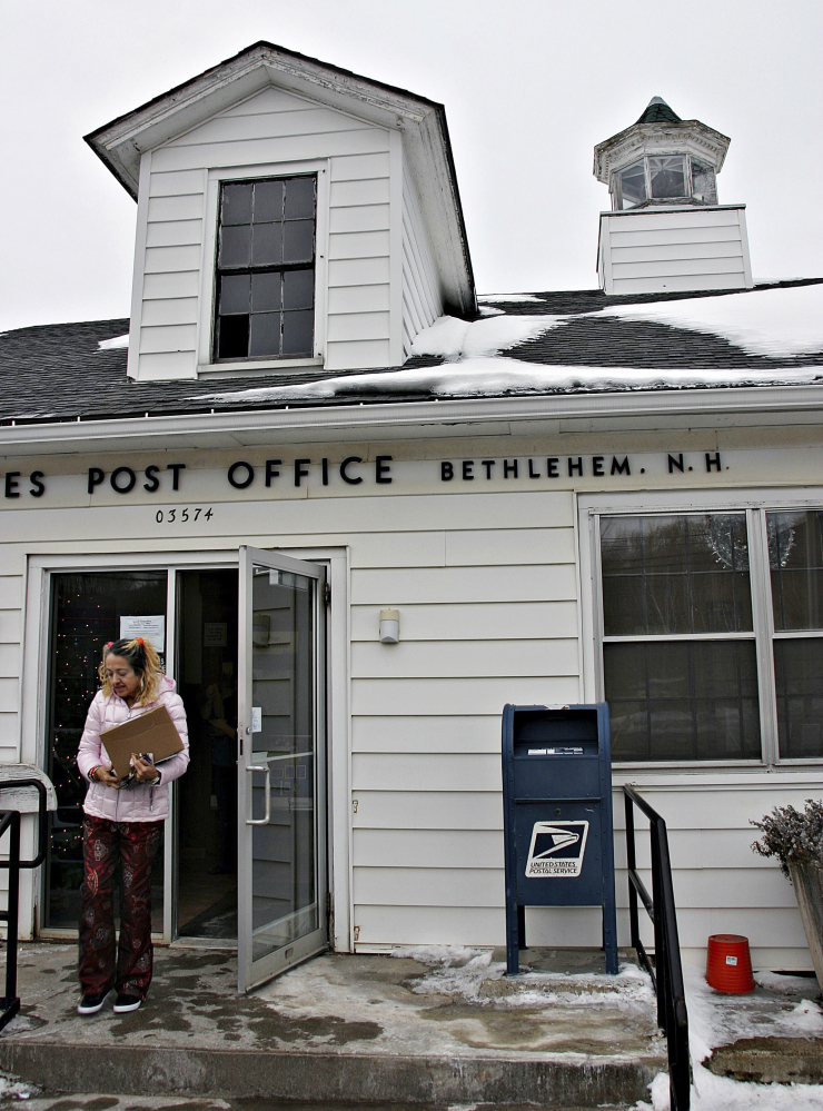 A patron leaves the post office in Bethlehem, N.H., on Tuesday. The tiny post office postmarked more than 58,000 pieces of holiday mail this year.