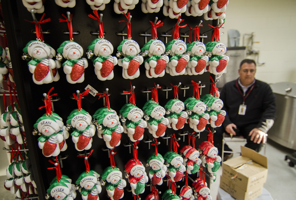 Fitchburg High School athletic director Ray Cosenza sits beside ornaments recently donated by Ornament Central to Fitchburg Public Schools for a fundraiser for the athletic department. Officials at Ornament Central, a family-owned wholesaler, said they will move 600,000 ornaments resulting in more than $1.6 million in sales.