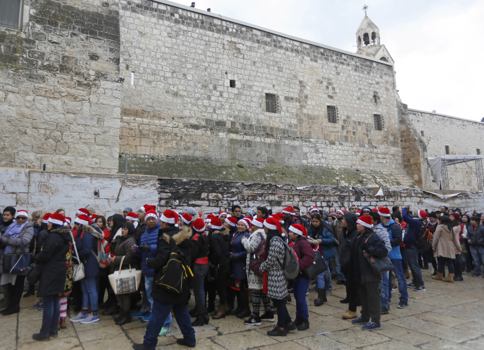 Christian pilgrims wearing red Santa hats wait in line to enter the Church of the Nativity, built atop the site where Christians believe Jesus Christ was born, on Christmas Eve.