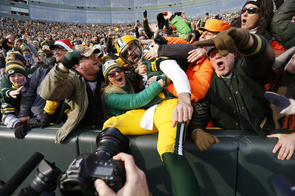 Packers quarterback Aaron Rodgers celebrates his touchdown run with fans during Saturday's game against the Minnesota Vikings. Green Bay stayed in playoff position with its fifth straight win – 38-25.