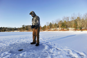 Cody McFarland drops a line in a fishing hole while ice fishing on Otter Ponds in Standish Friday.